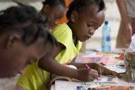 A young Haitian girl colors in an activity book at the HATS home base.