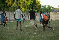 Roma Team members playing soccer with local children.